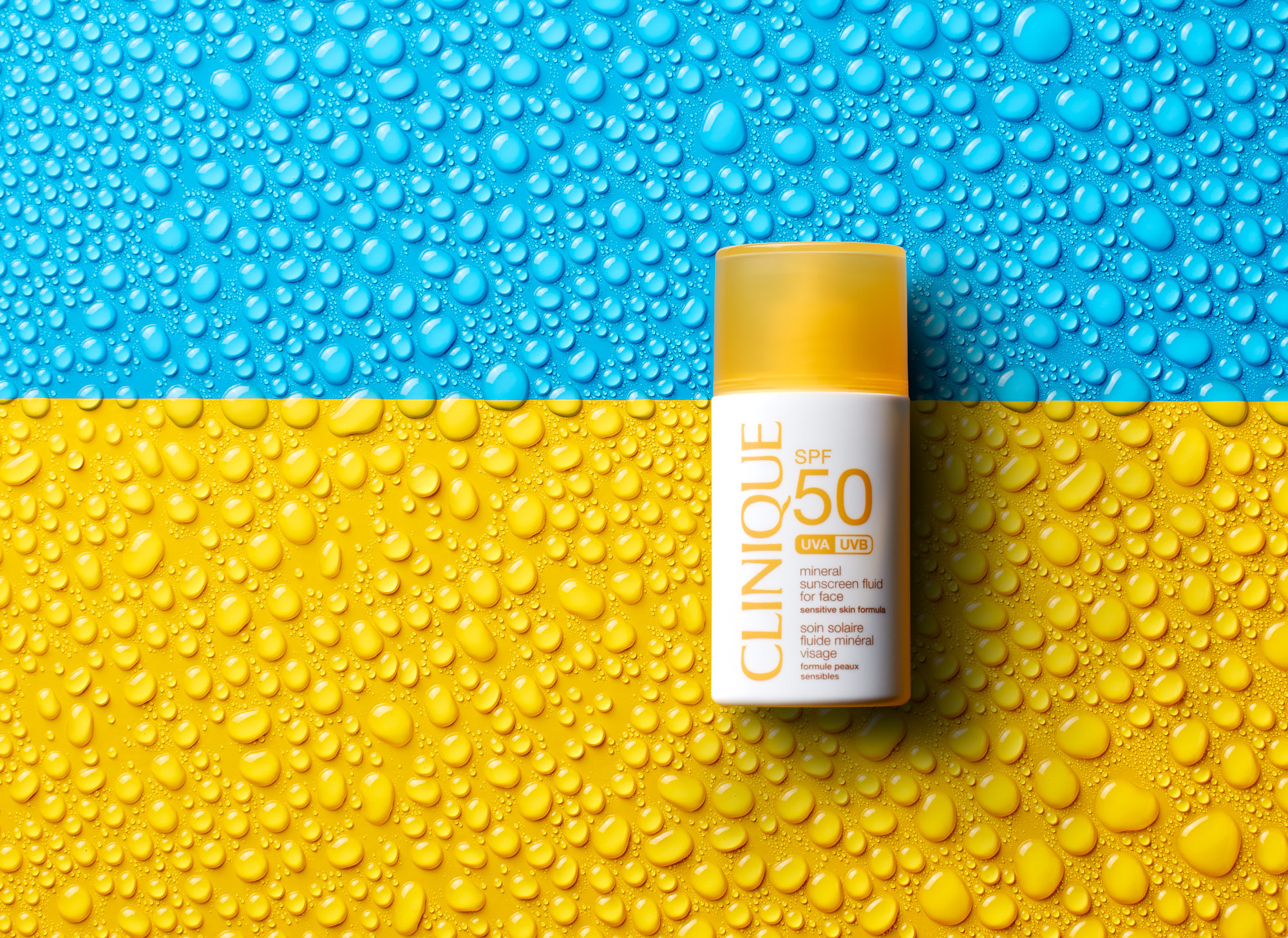 Clinique waterproof sunscreen on color blocked background with water droplets.