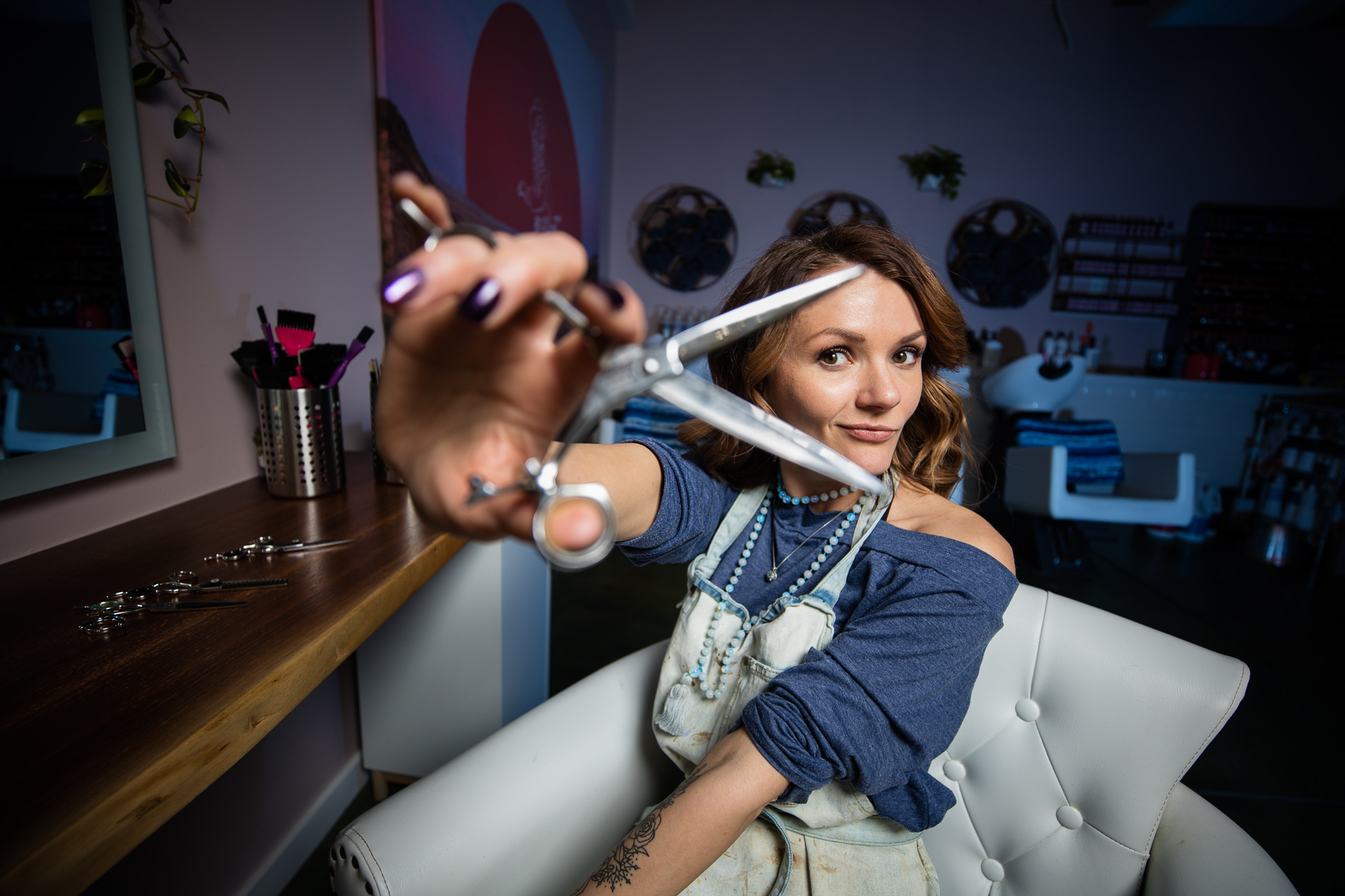 Lifestyle photo portrait of hair stylist holding up scissors in Boulder, Colorado.