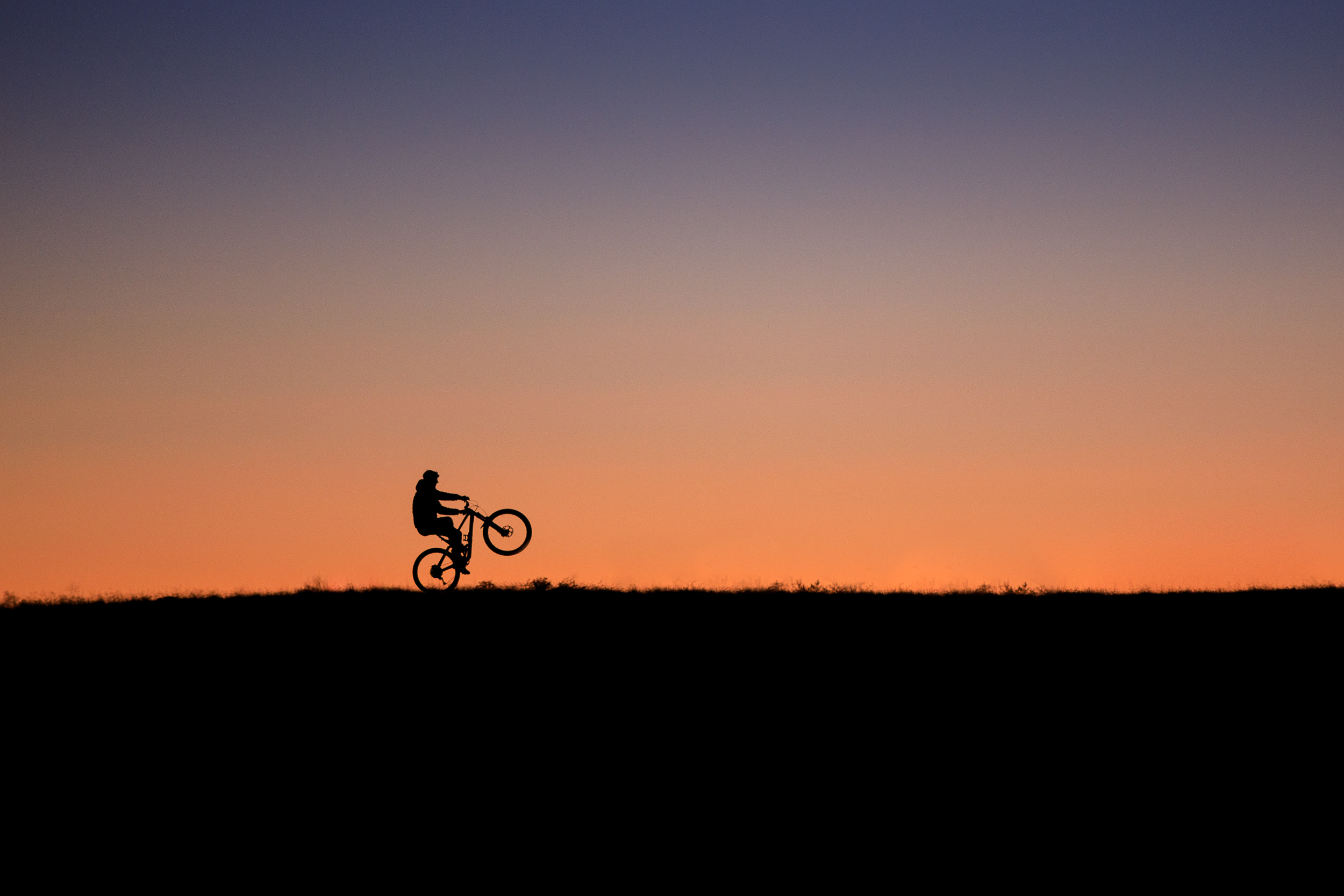 Mountain biker doing a wheelie silhouetted against the sunset in Fruita Colorado.