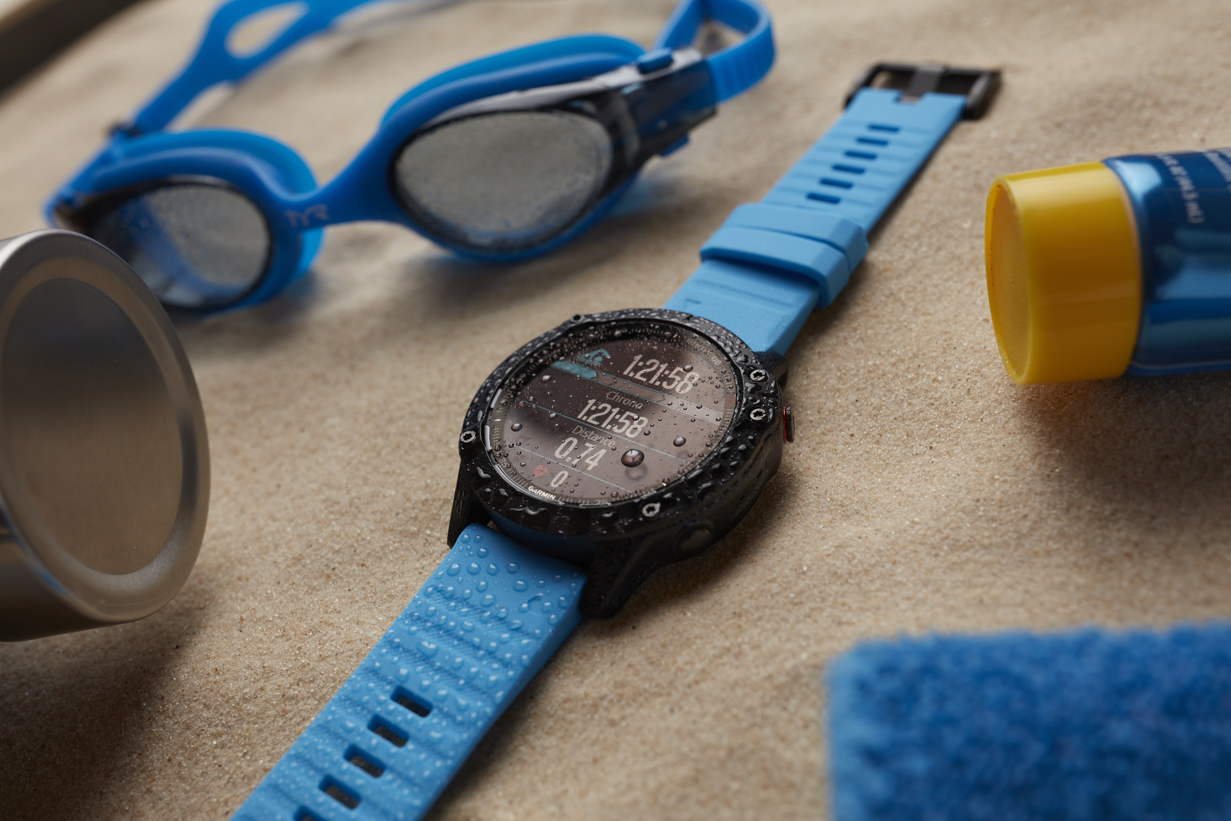 Close up lifestyle product photo of a Garmin Fenix 6 multisport watch in a still life beach scene.