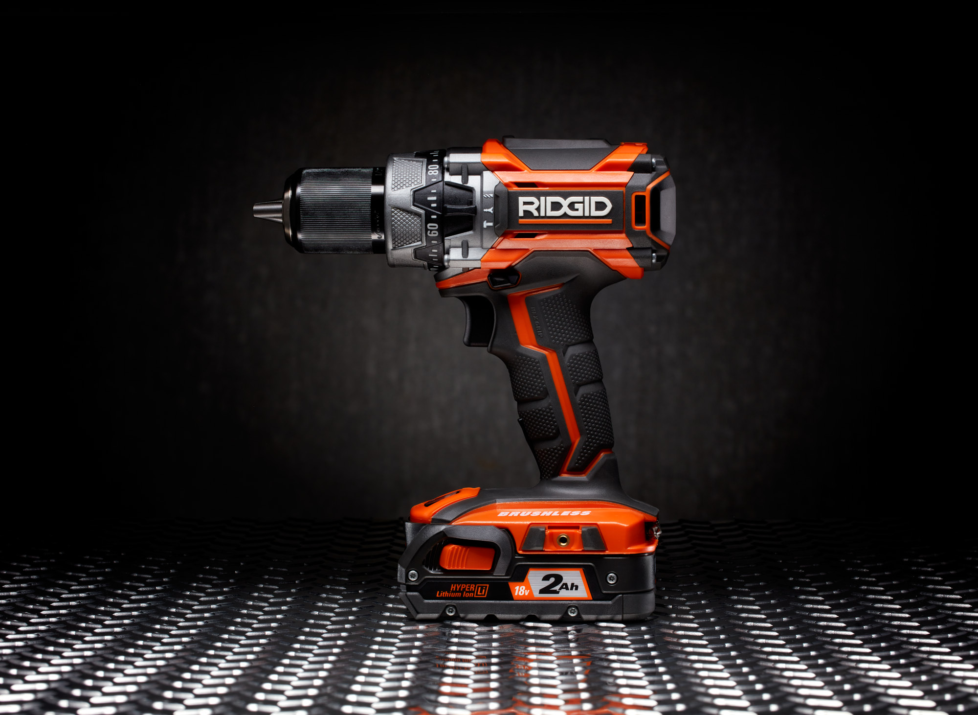 RIDGID-Drill studio product photo on diamond plate with concrete wall in background.