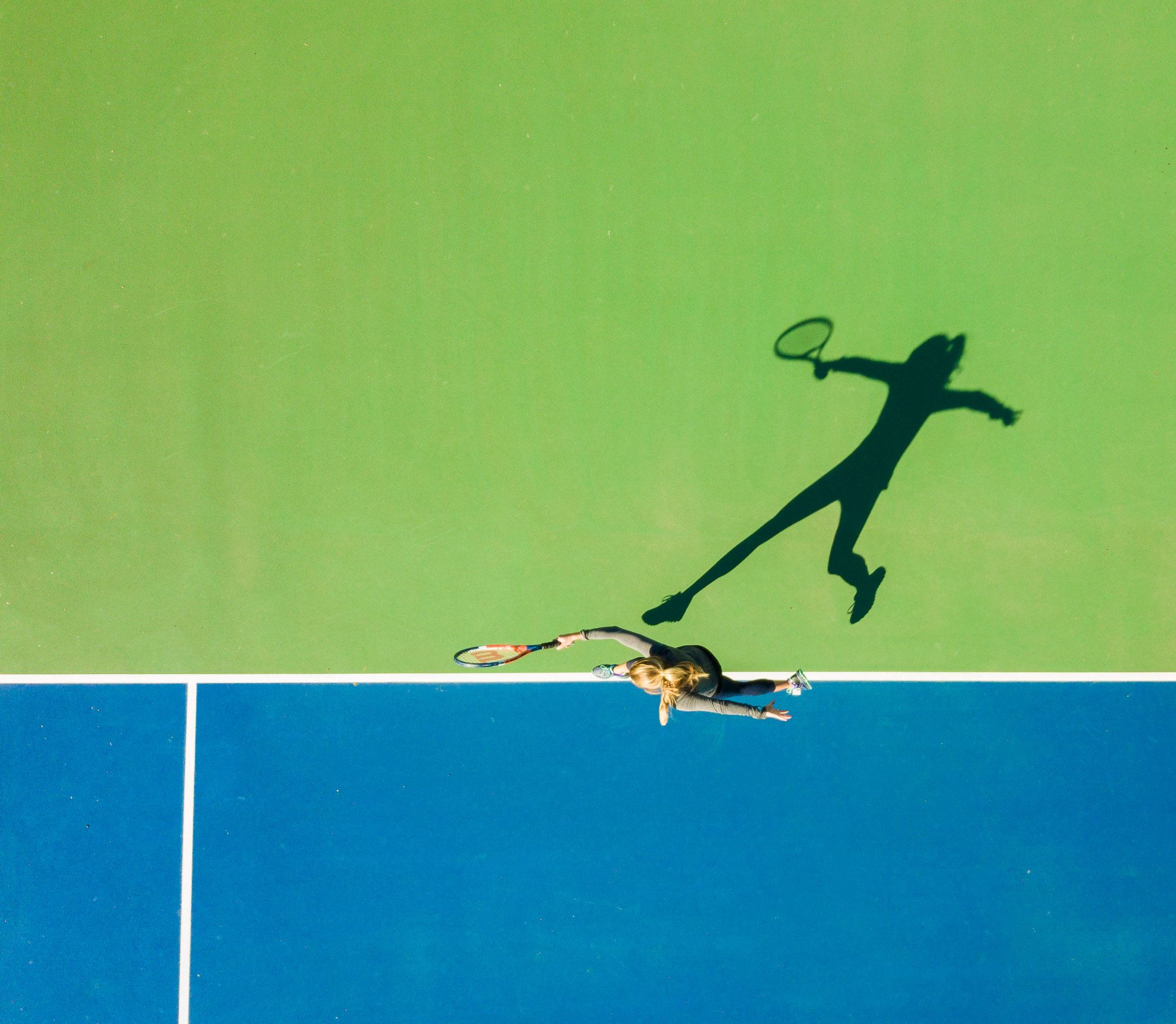 Aerial drone photo of a girl playing tennis casting a shadow on the court.