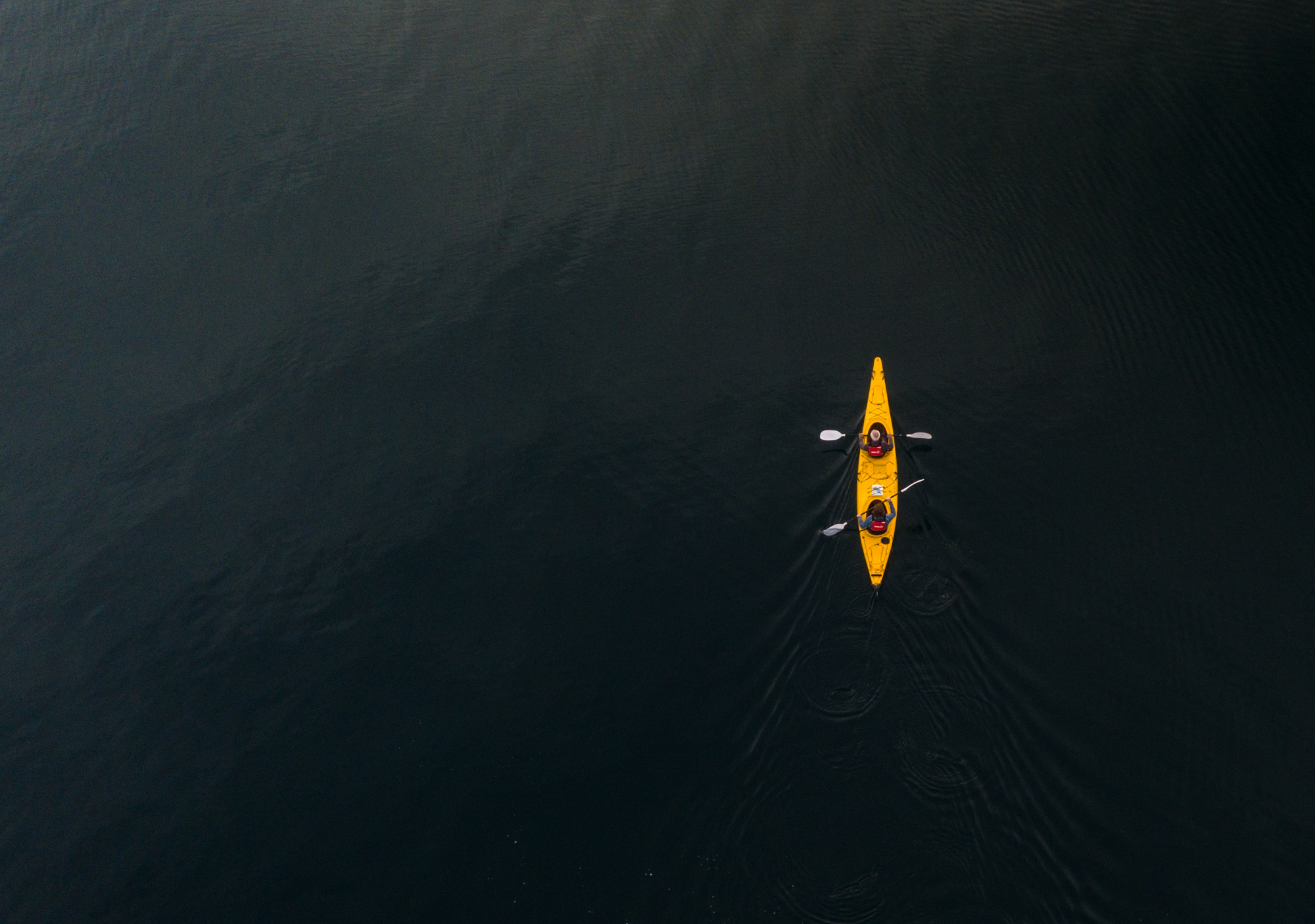 Lifestyle aerial drone photo of two people kayaking in yellow kayak in Wanaka, New Zealand.