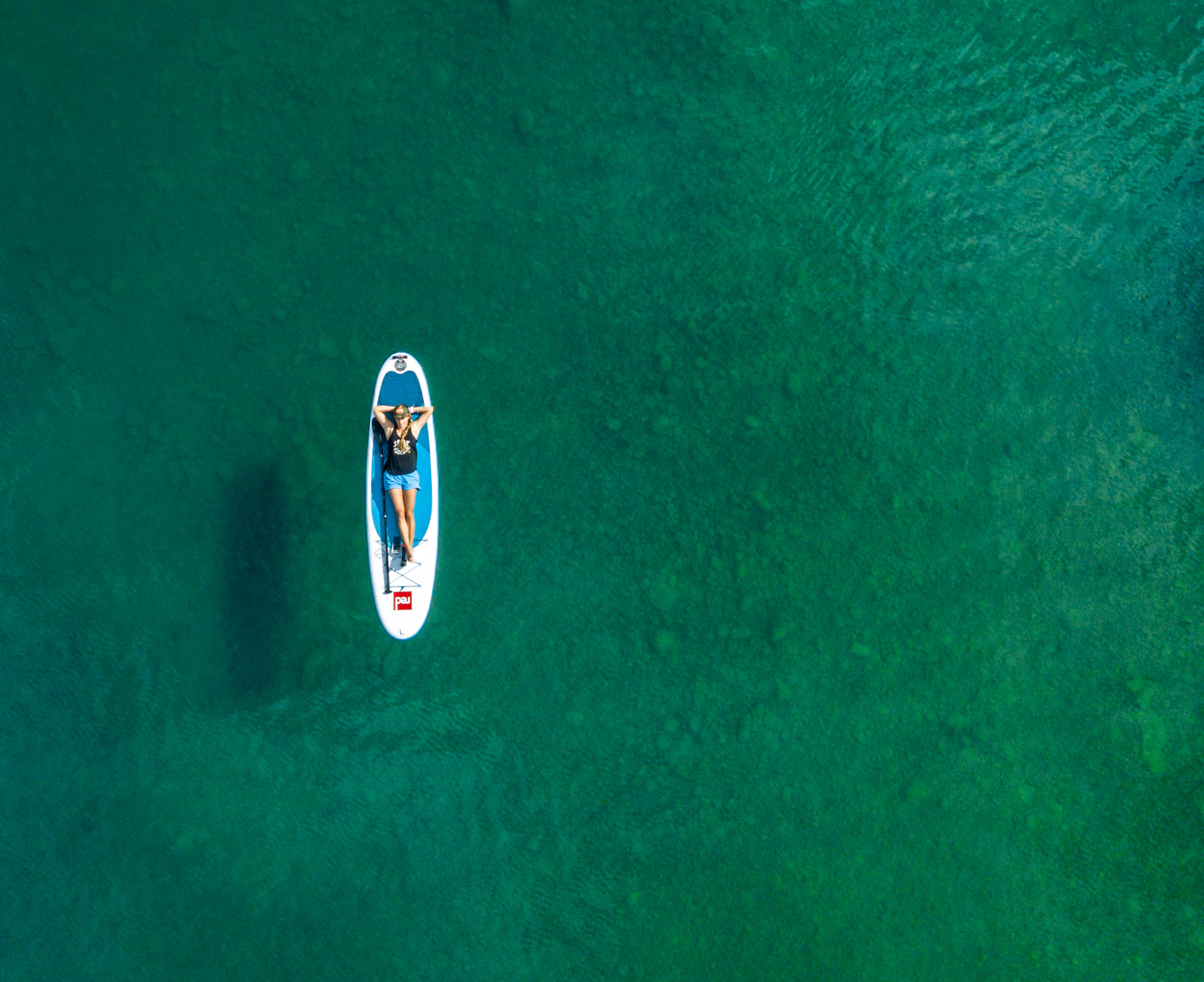 Active lifestyle Aerial drone  photo of girl lying on Red Paddle Company SUP in Lake Chelan, Washington.