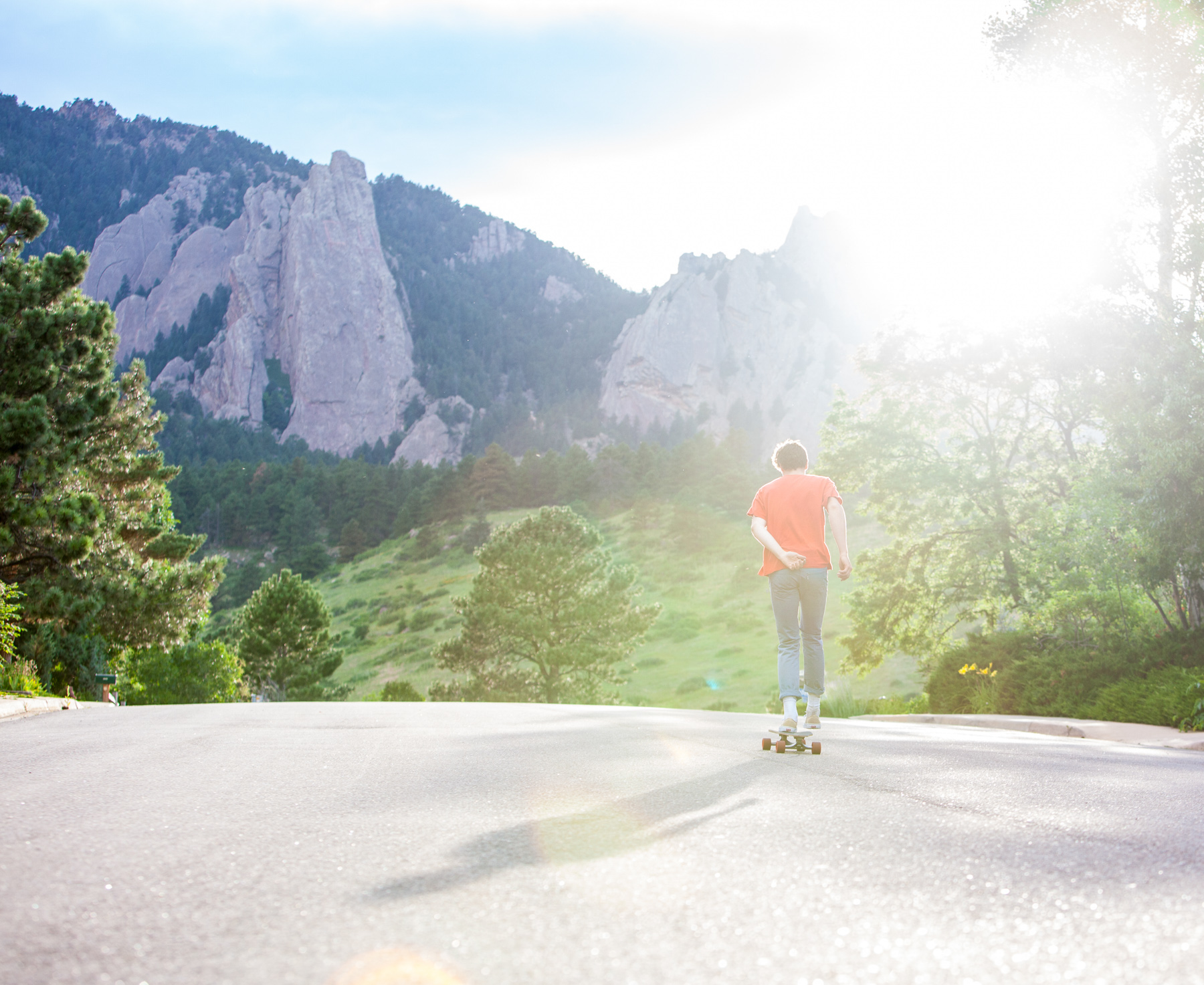 Lifestyle photo of guy skateboarding uphill with Flatirons mountains behind in Boulder, Colorado.