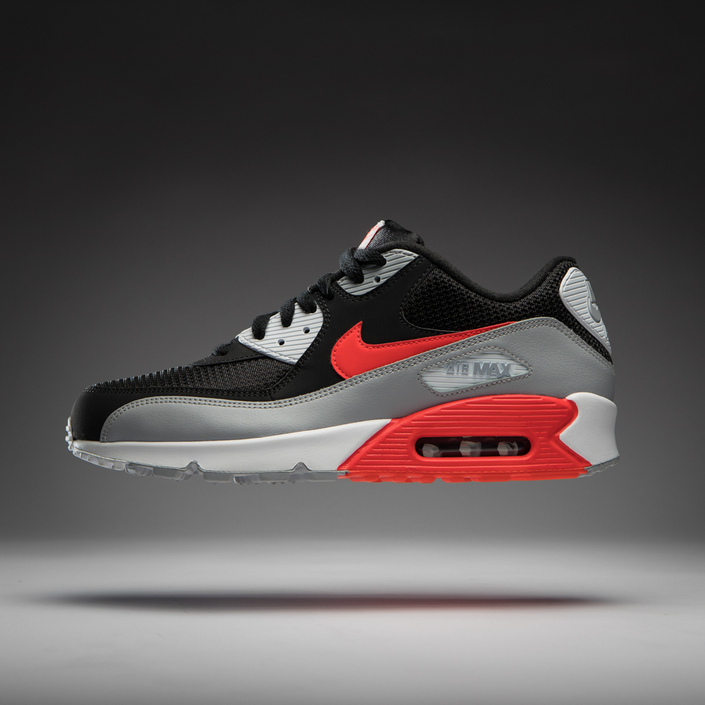 Floating product photo of Nike Air Max 90 Essential sneaker shoe on white background with gradient.