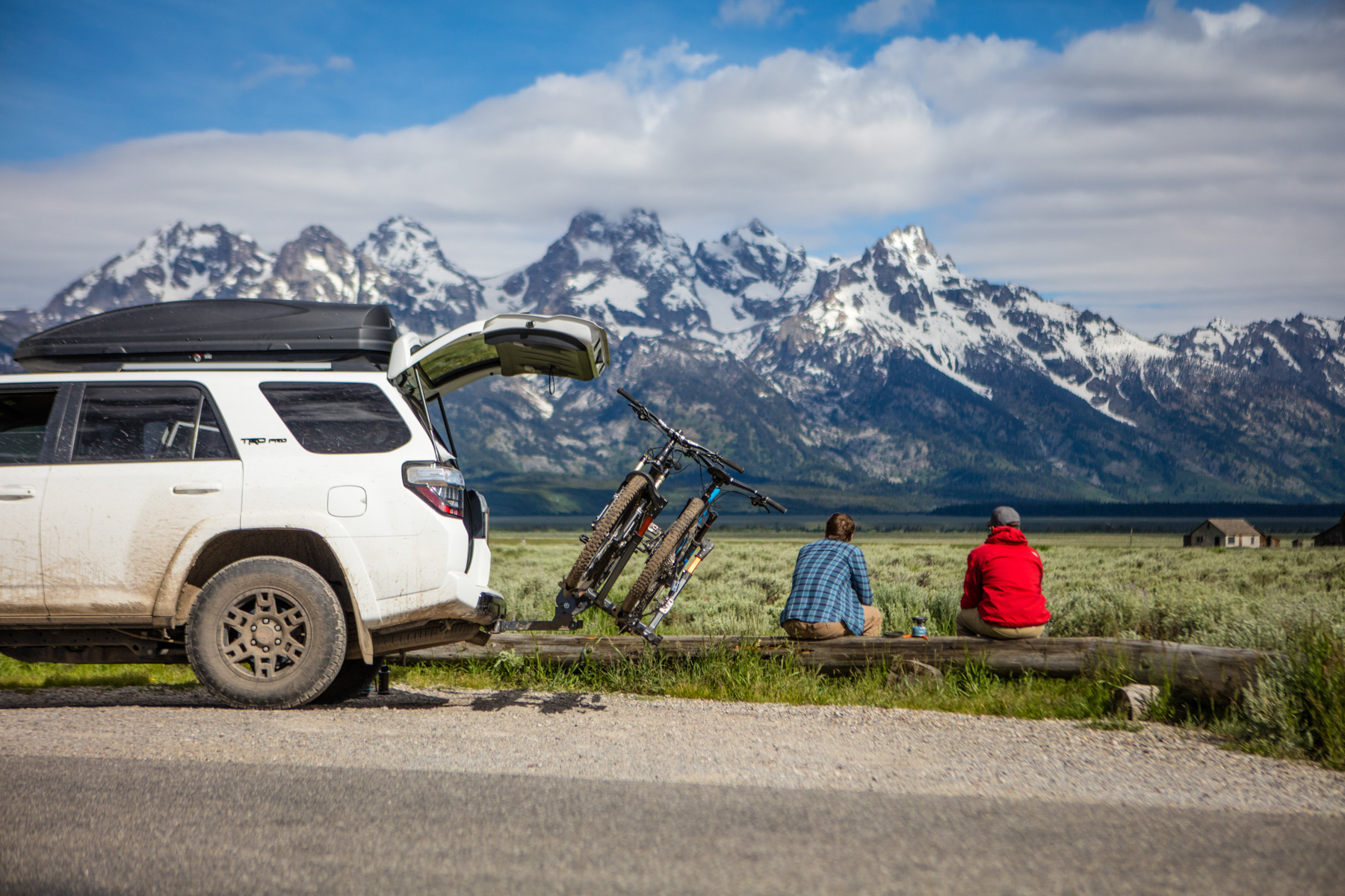 Active lifestyle photo of two guys sitting on a log next to a Toyota 4runner watching the Tetons in Wyoming.