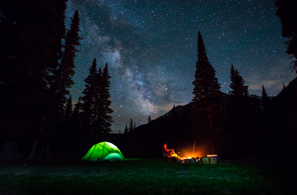 Active lifestyle night photo of Nemo tent and guy sitting by fireplace with Milky Way in Bozeman, Montana.