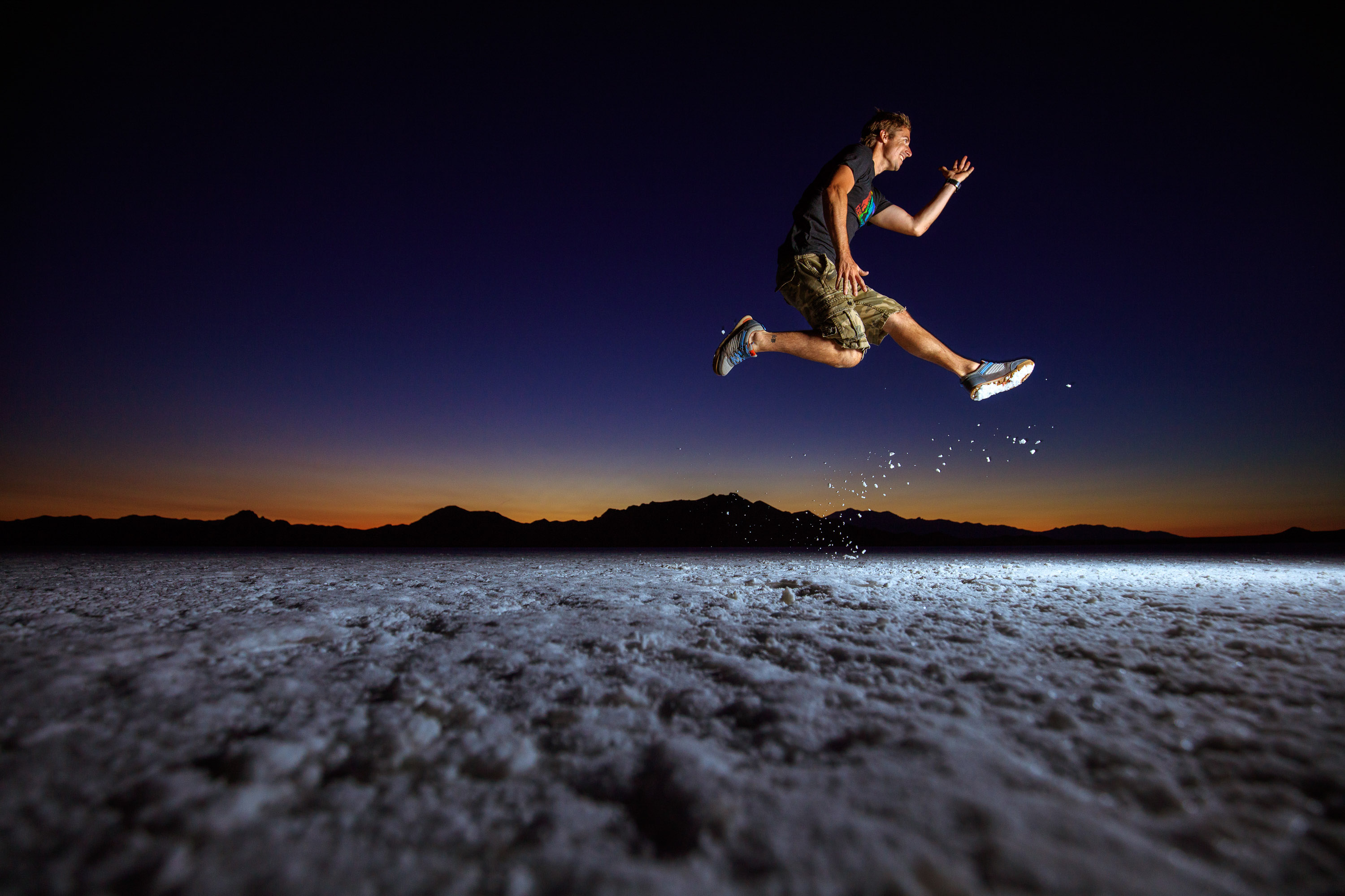 Shoe lifestyle photo of guy doing a jump at dusk on Bonneville salt flats in Utah.