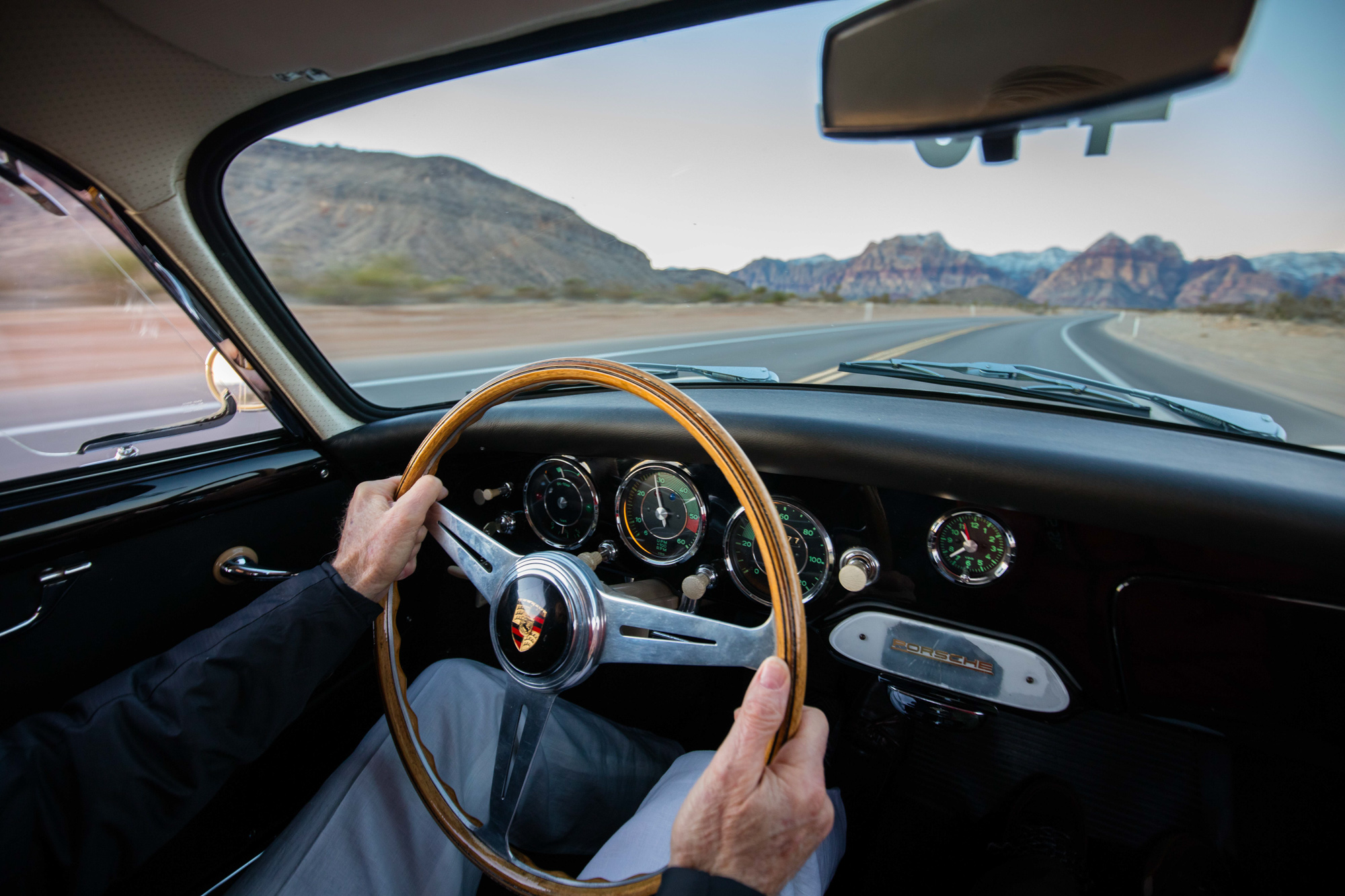 Lifestyle photo of man driving a vintage Porsche in Red Rocks, Nevada.