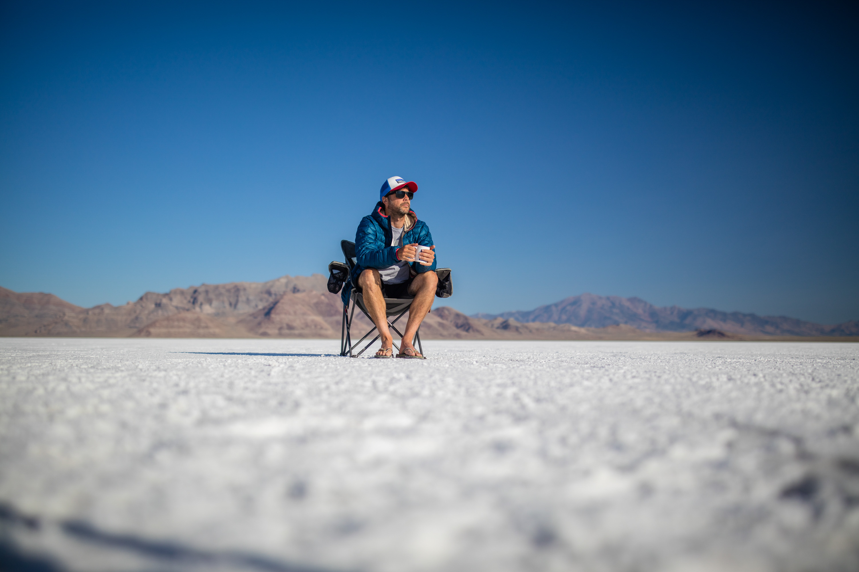 Lifestyle photo of guy sitting on chair on the Bonneville Salt Flats in Utah.