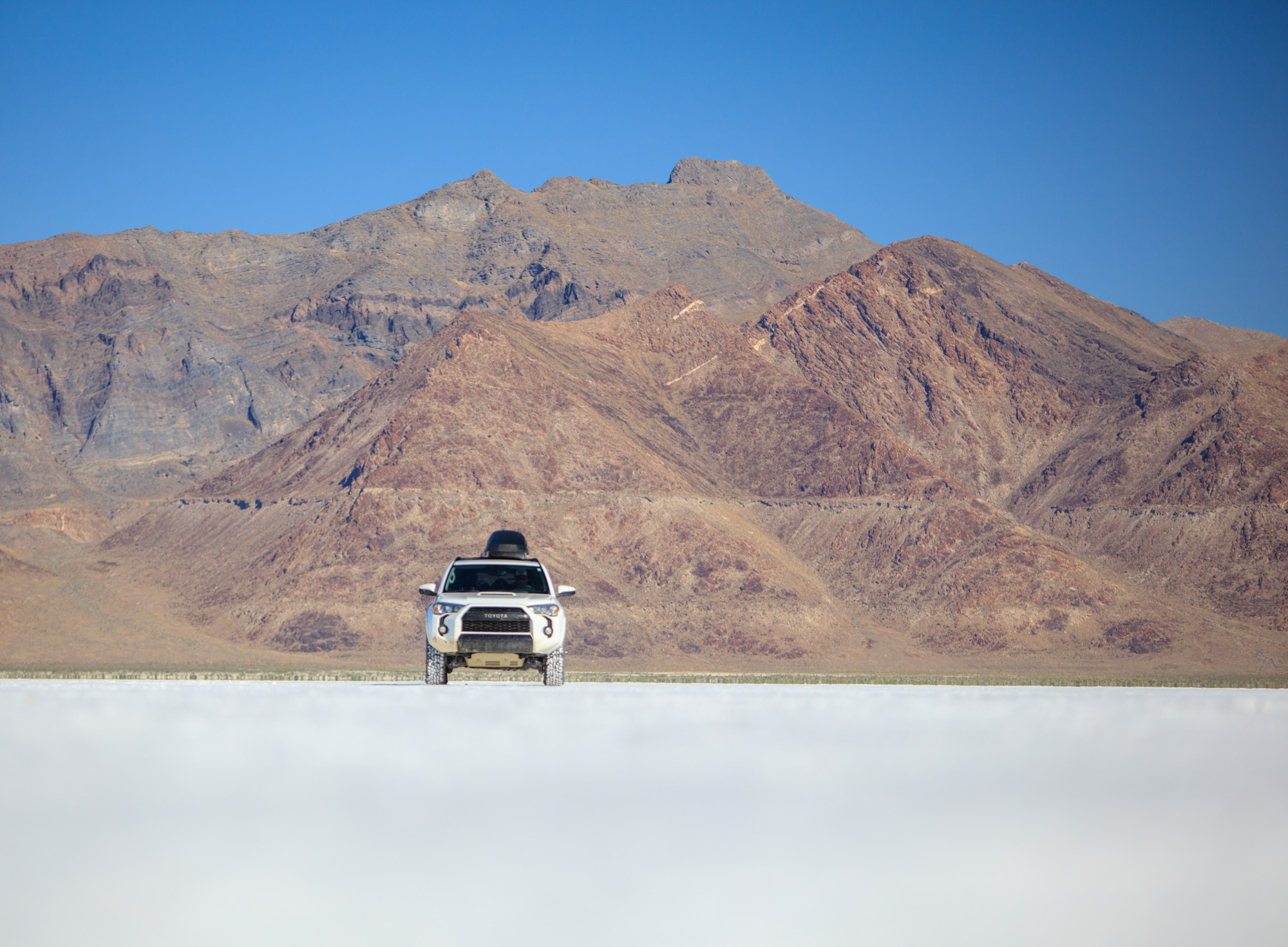 Toyota 4runner on the Bonneville Salt Flats in Utah with mountains in the background.