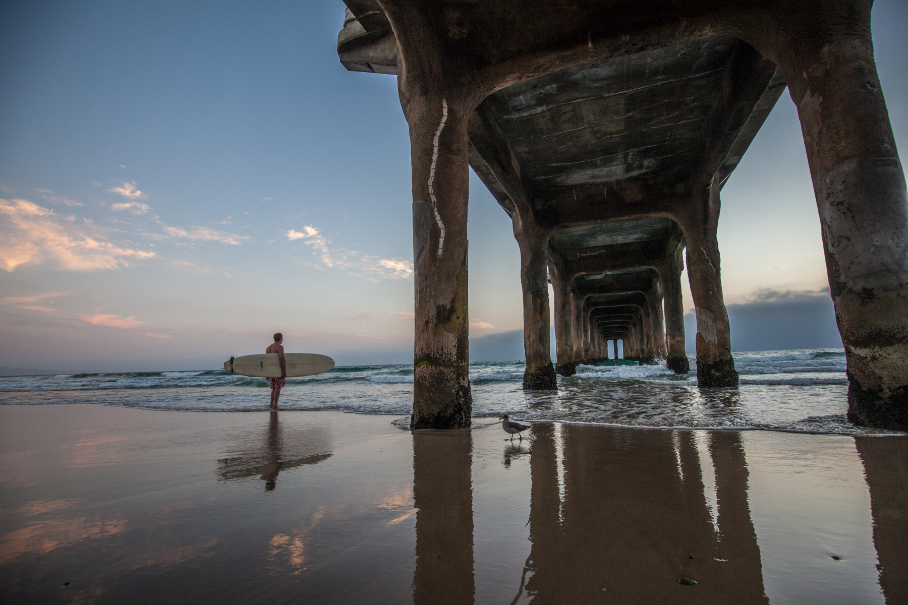 Lifestyle photo of longboard surfer about to paddle out near Huntington Pier in California.