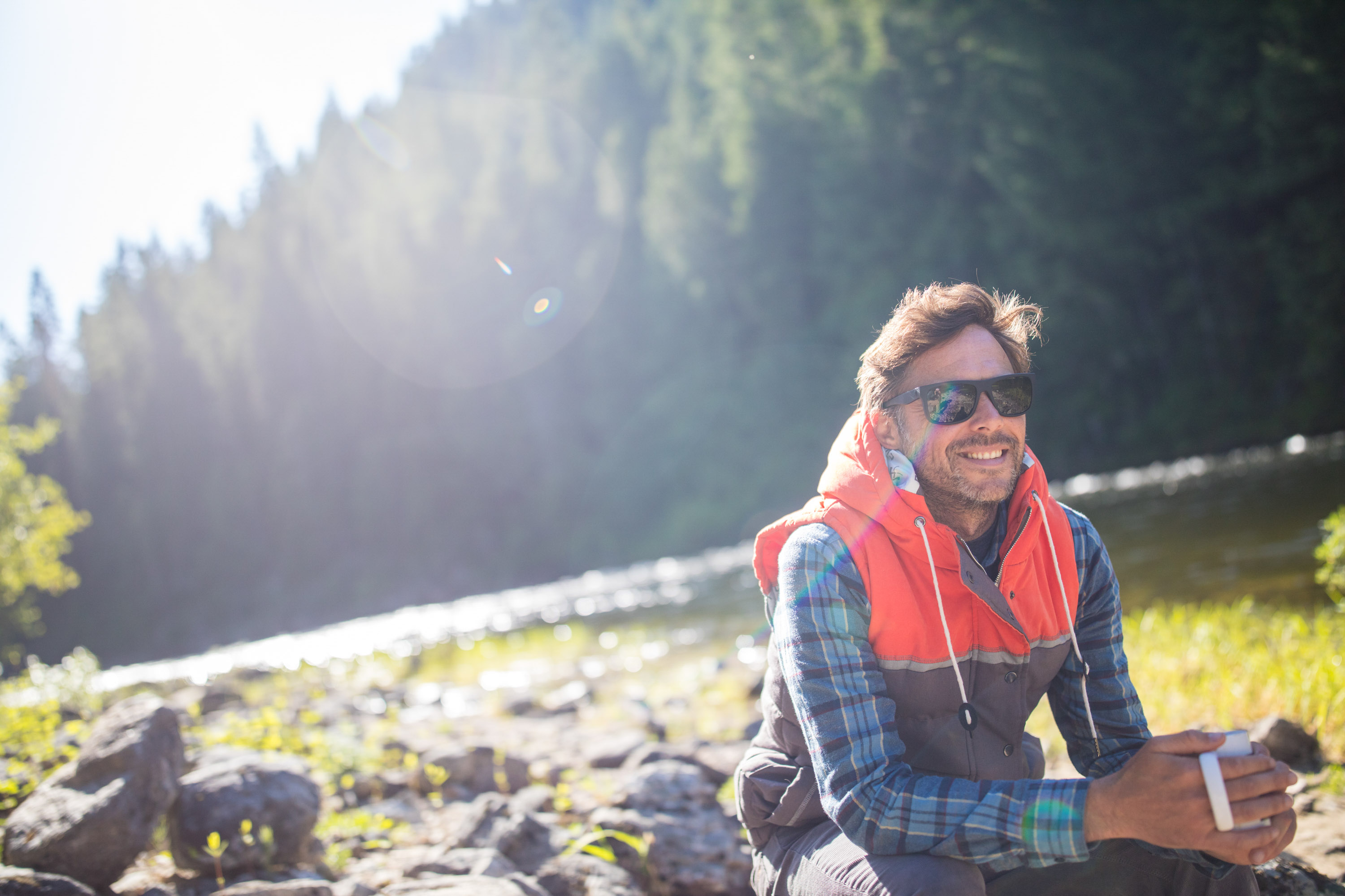 Lifestyle photo of guy sitting on log next to river drinking coffee in the morning in  Idaho.