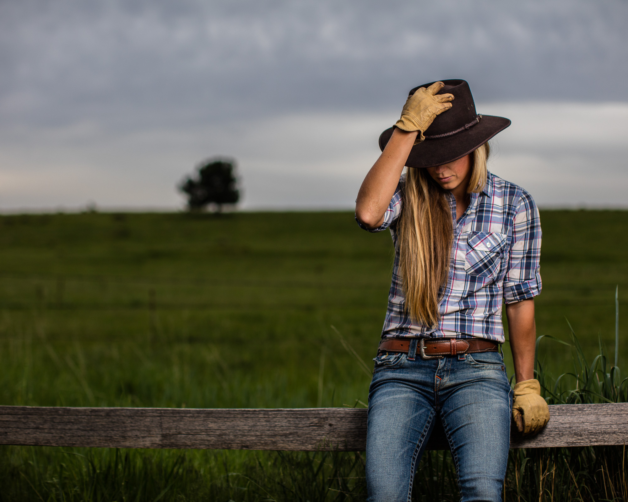 Active Lifestyle photo of blonde cowgirl with stetson hat sitting on fence on ranch.