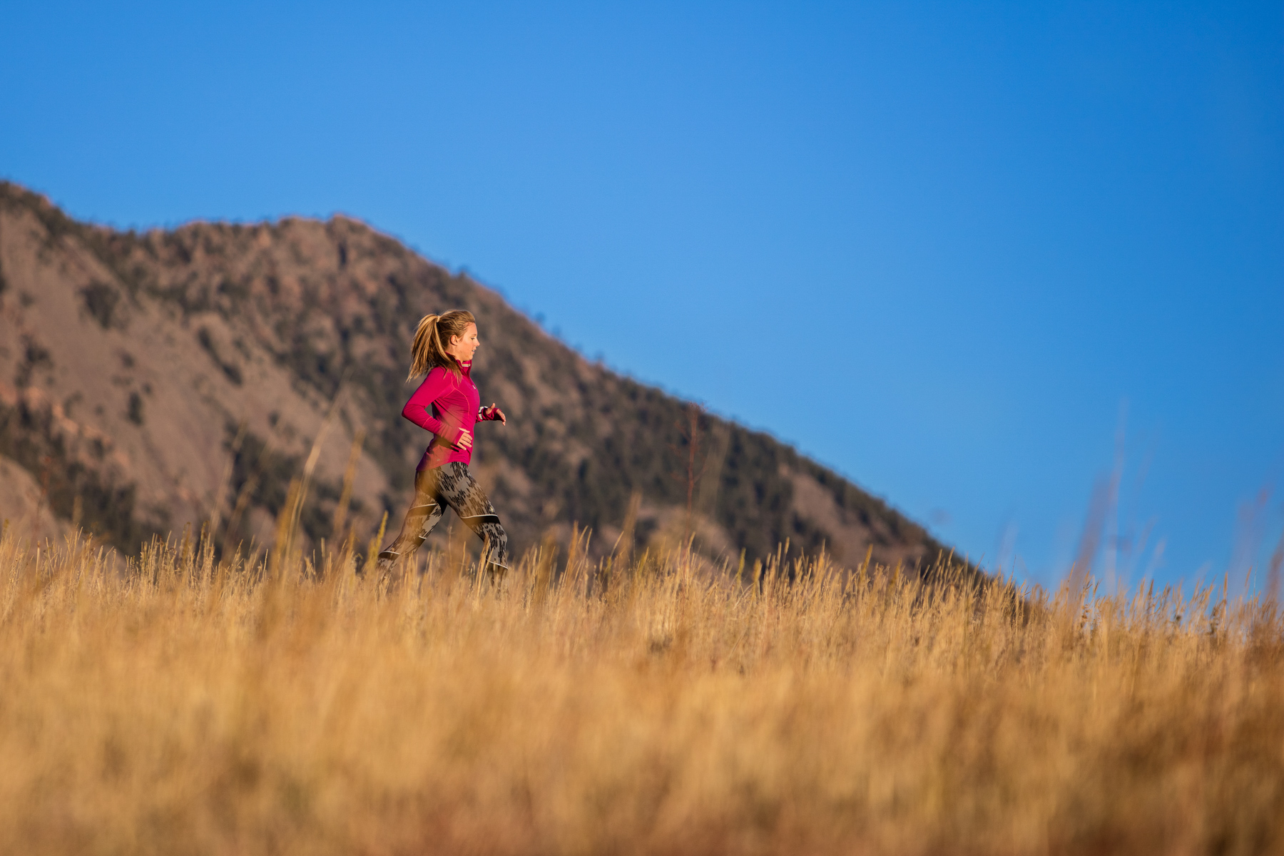 Lifestyle photo of girl running in SmartWool apparel with Flatiron mountains behind in Boulder, Colorado.