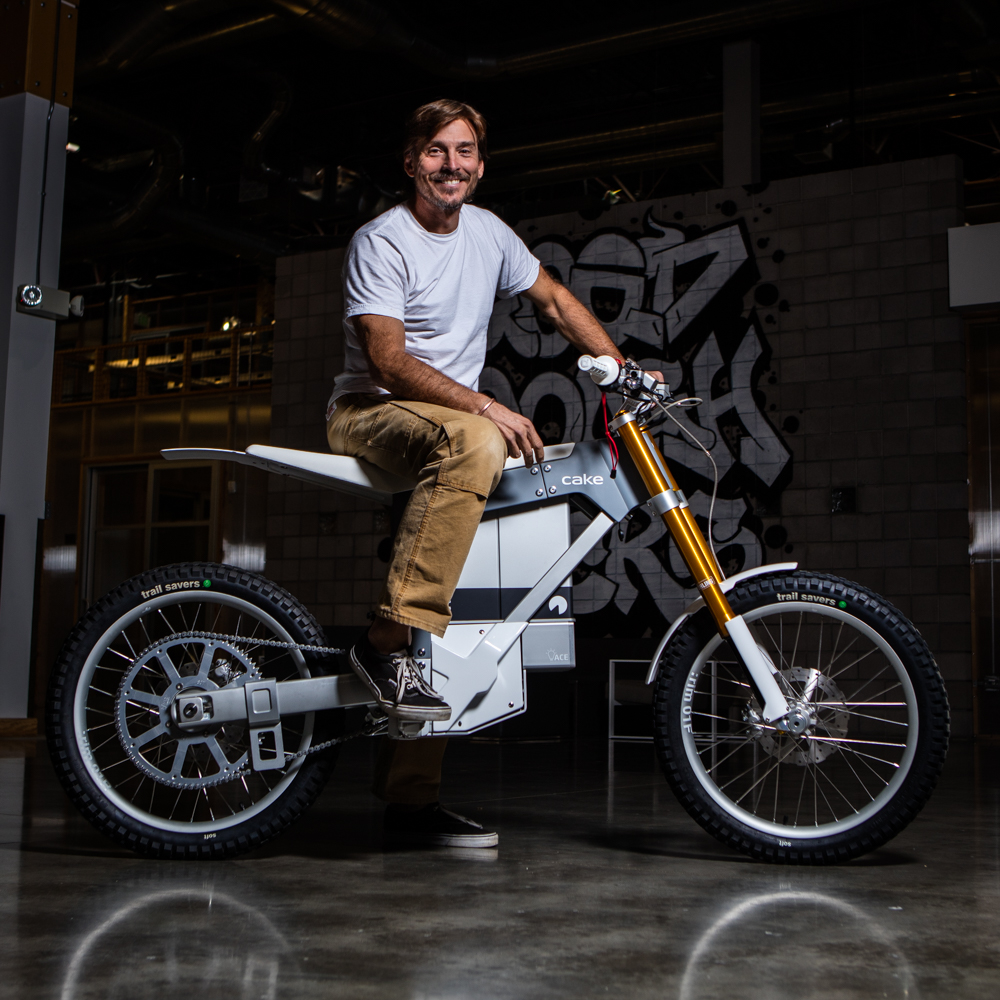Environmental portrait of Alex Bogusky standing by  a CAKE electric motorcycle at Crispin Porter agency in Boulder, Colorado.