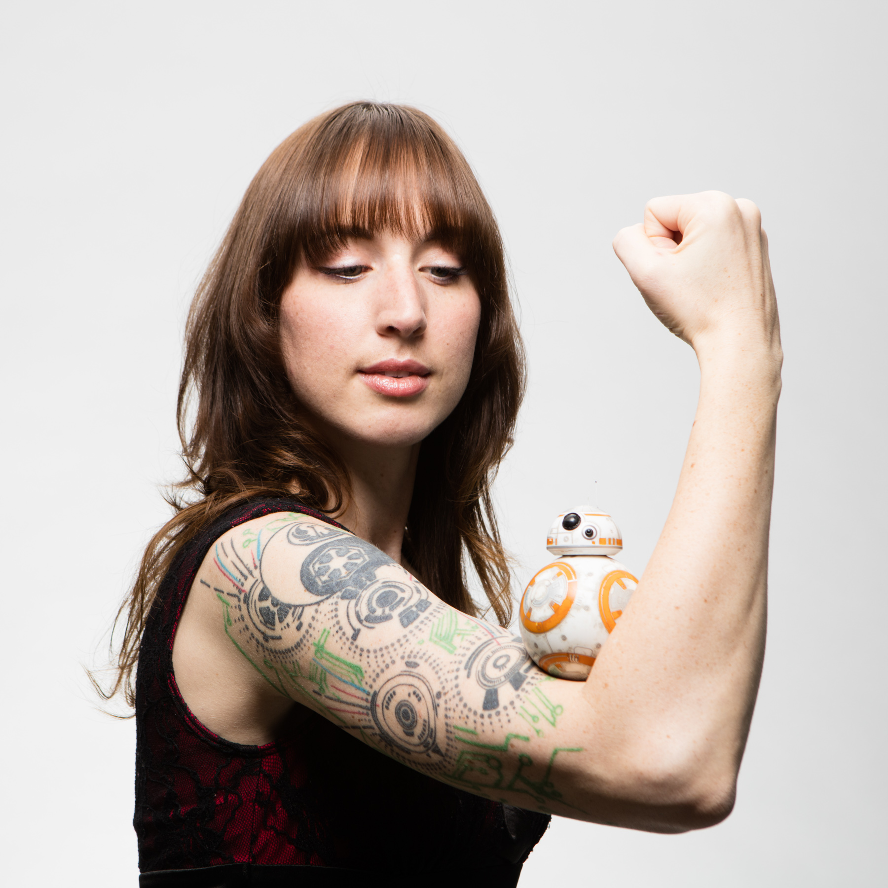 Portrait of girl flexing her muscles with BB-8 in the nook of her arm.