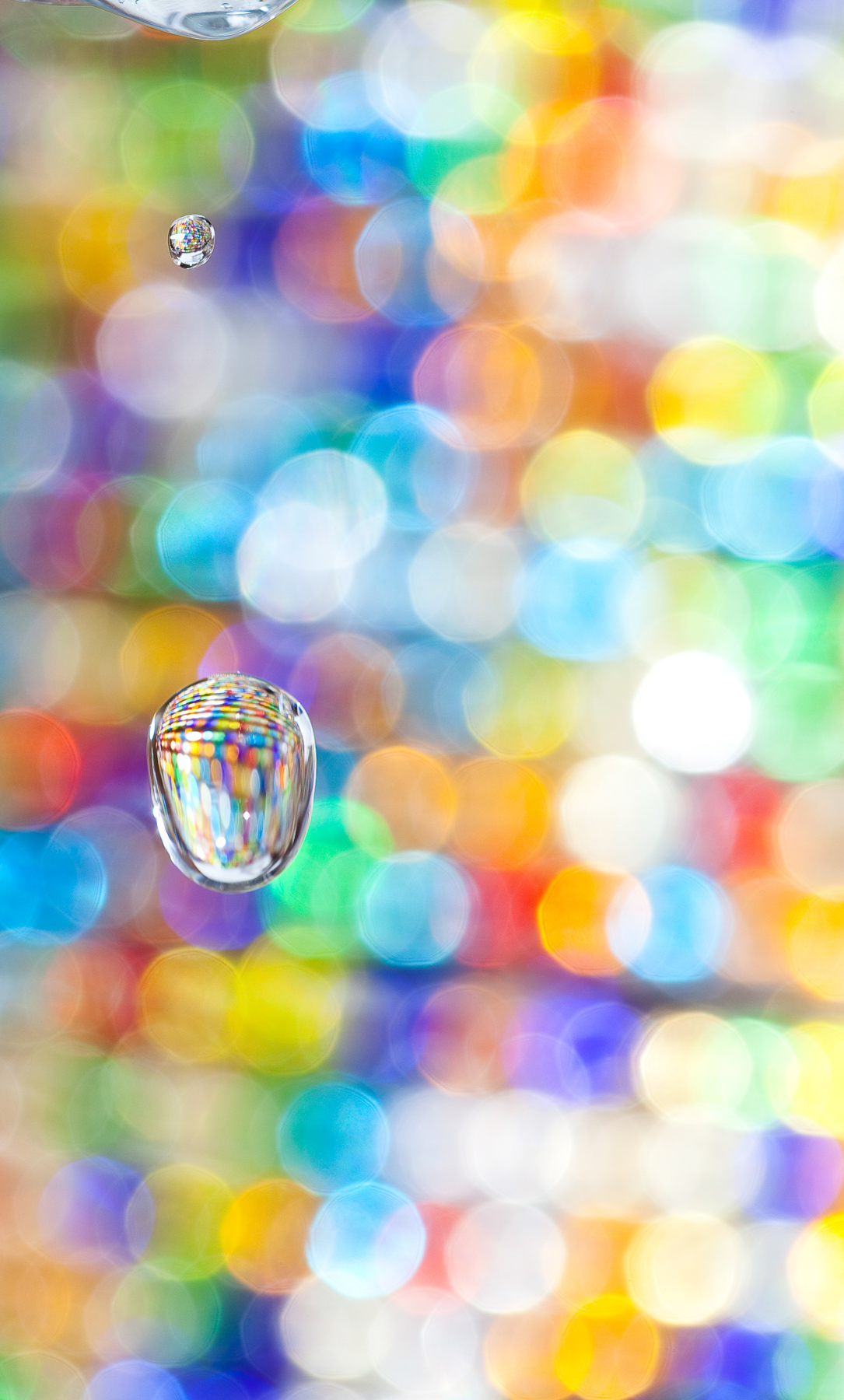 Macro Fine Art photo of a single water drop in the air refracting colored beads in the background.