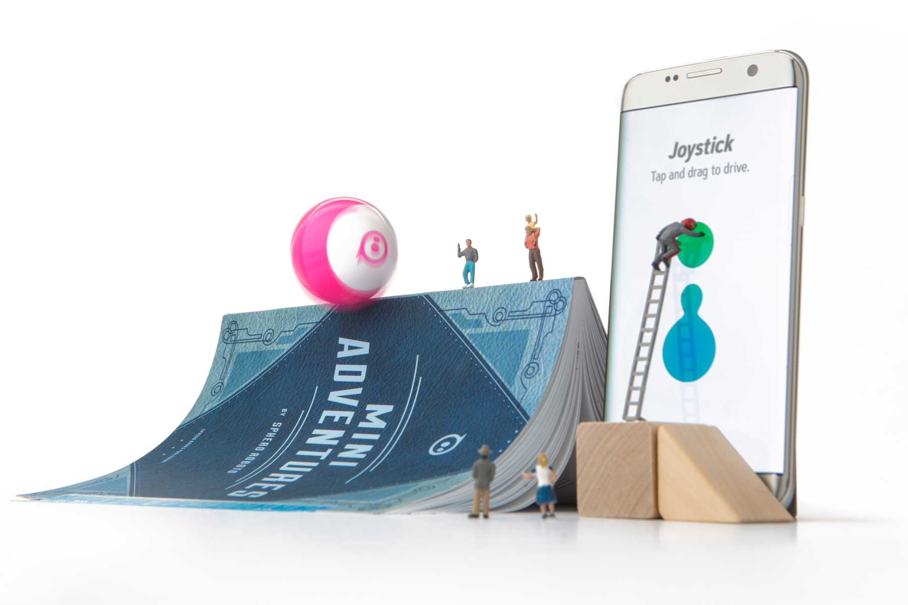 Sphero MiNi  doing a trick on  a book with mini people all around.