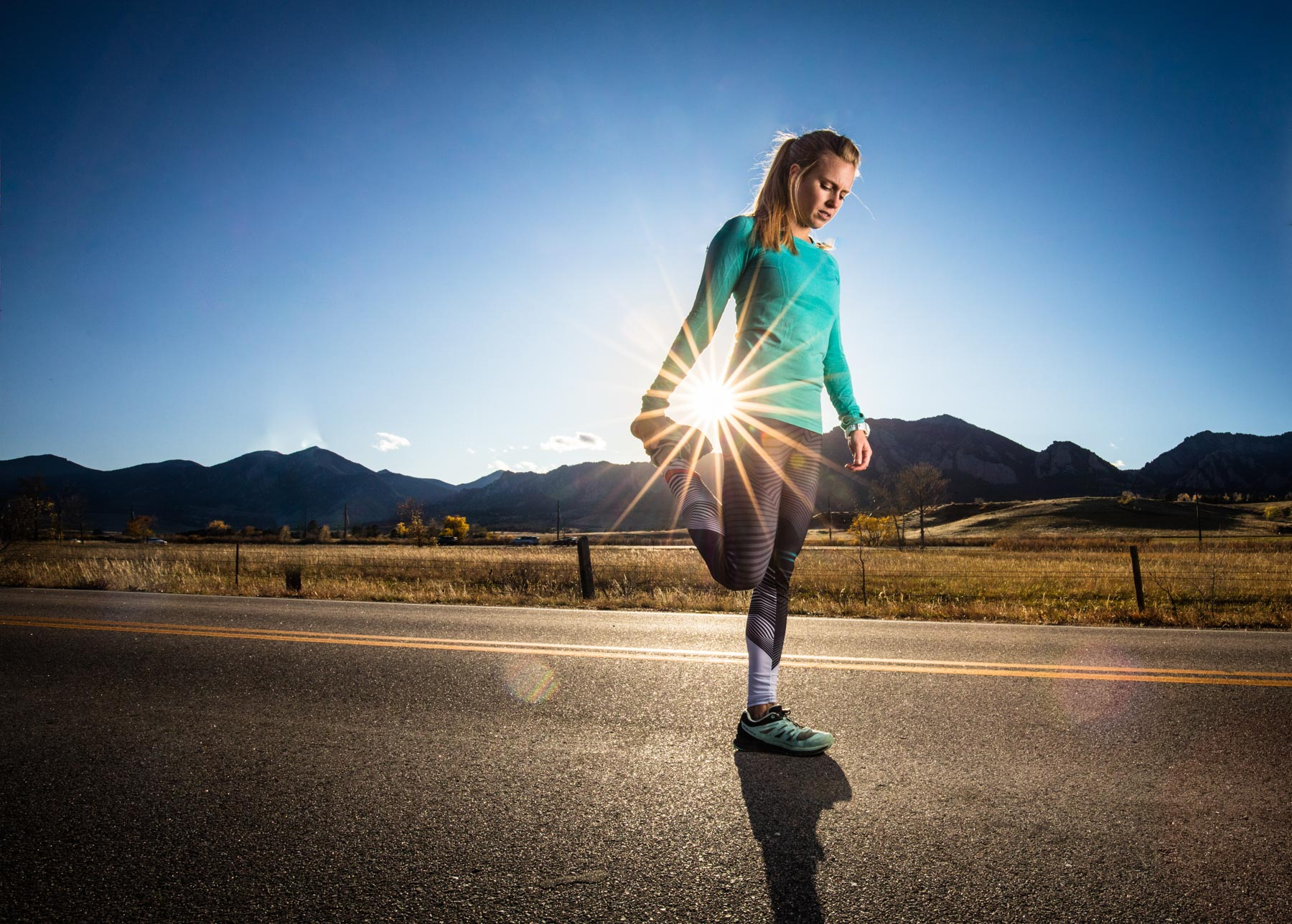 Active lifestyle photo of runner girl stretching on the road in Boulder, Colorado with sun streaming through.