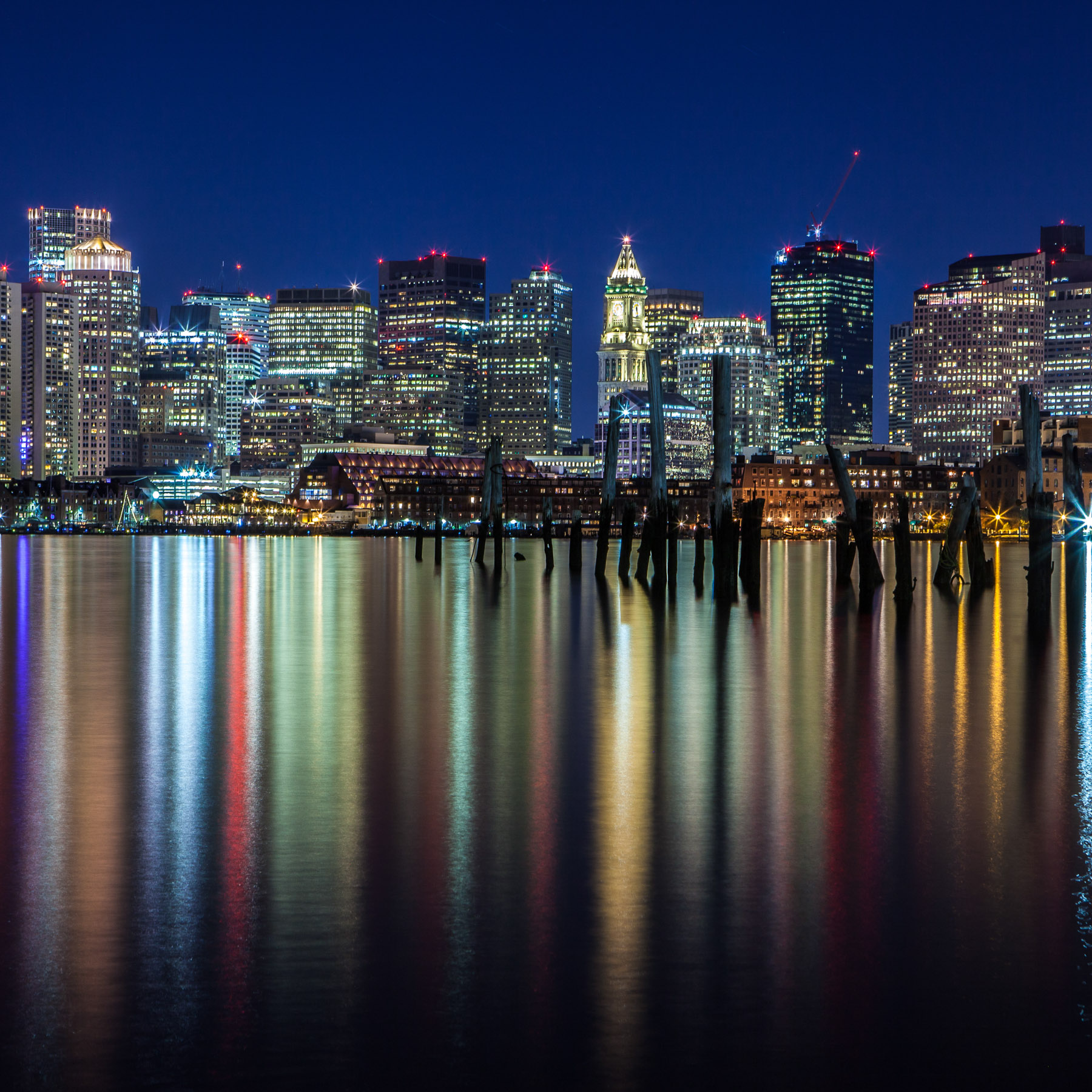 Boston skyline at night reflecting lights of the buildings.