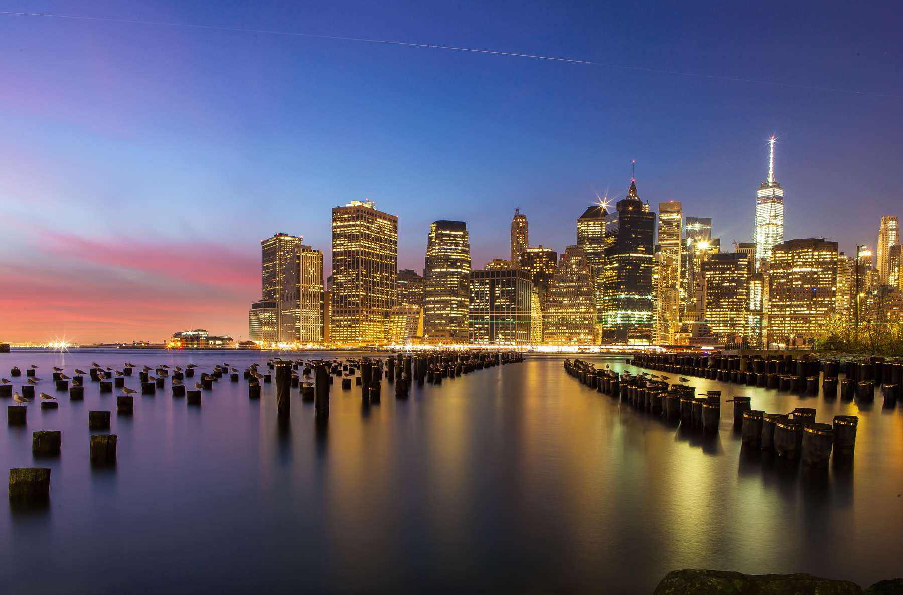 Manhattan skyline from Brooklyn Bridge Park at dusk in New York City.