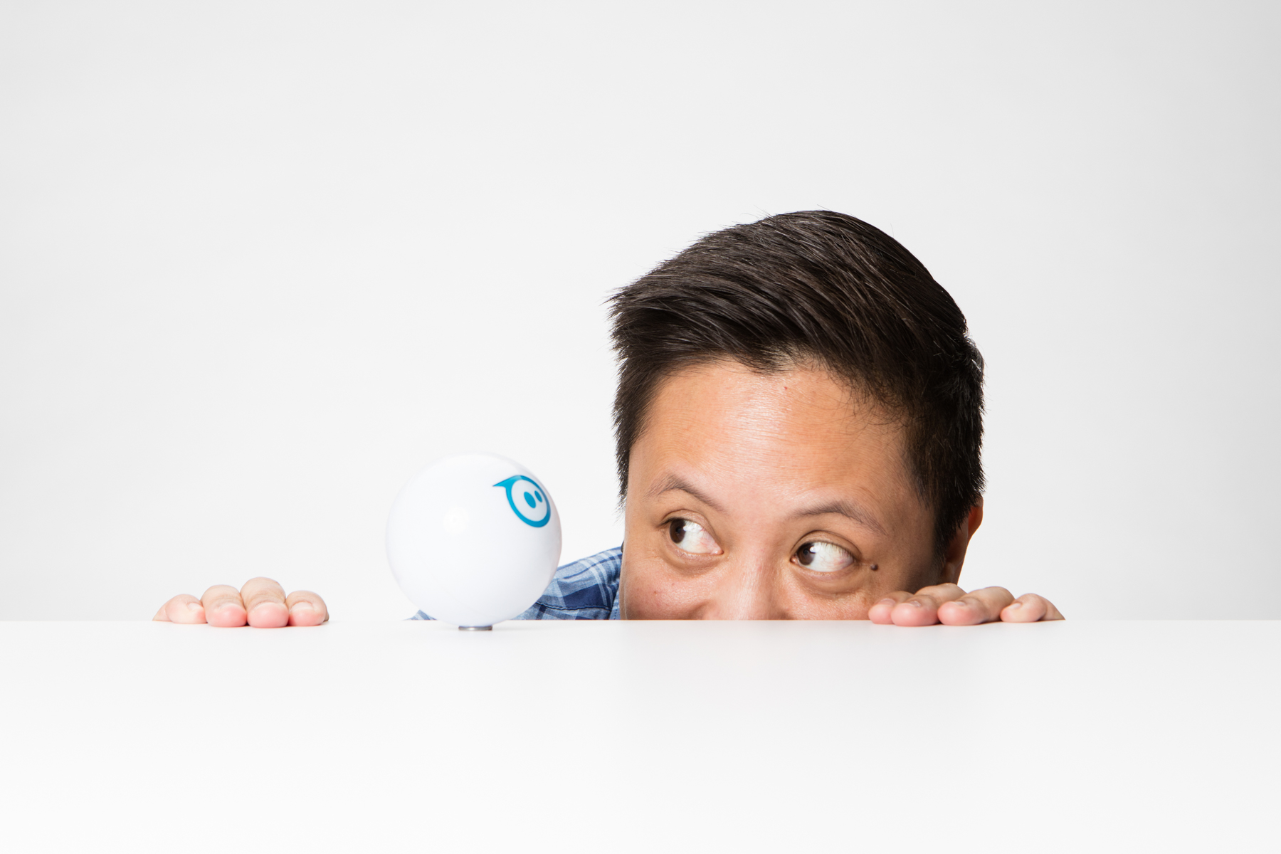 Portrait of women peaking at a Sphero robot in Boulder, Colorado.