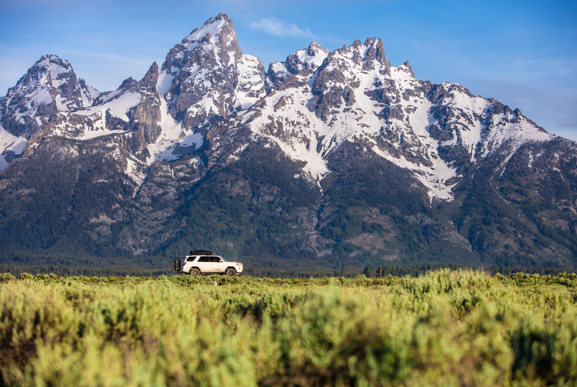 Toyota 4runner with Kuat bike rack driving in front of the tetons in Wyoming.