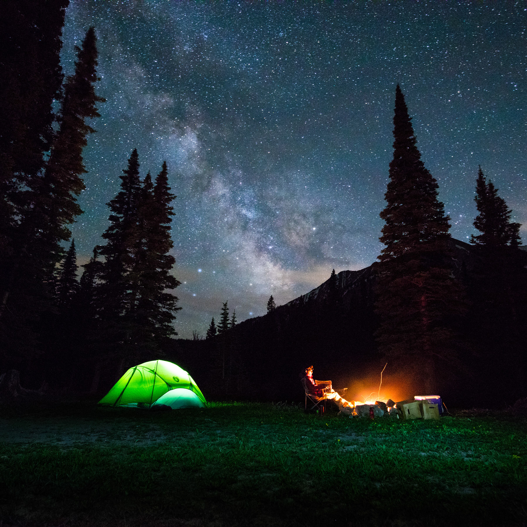 Lifestyle night photo of Nemo tent and guy sitting by fireplace with Milky Way in Bozeman, Montana.
