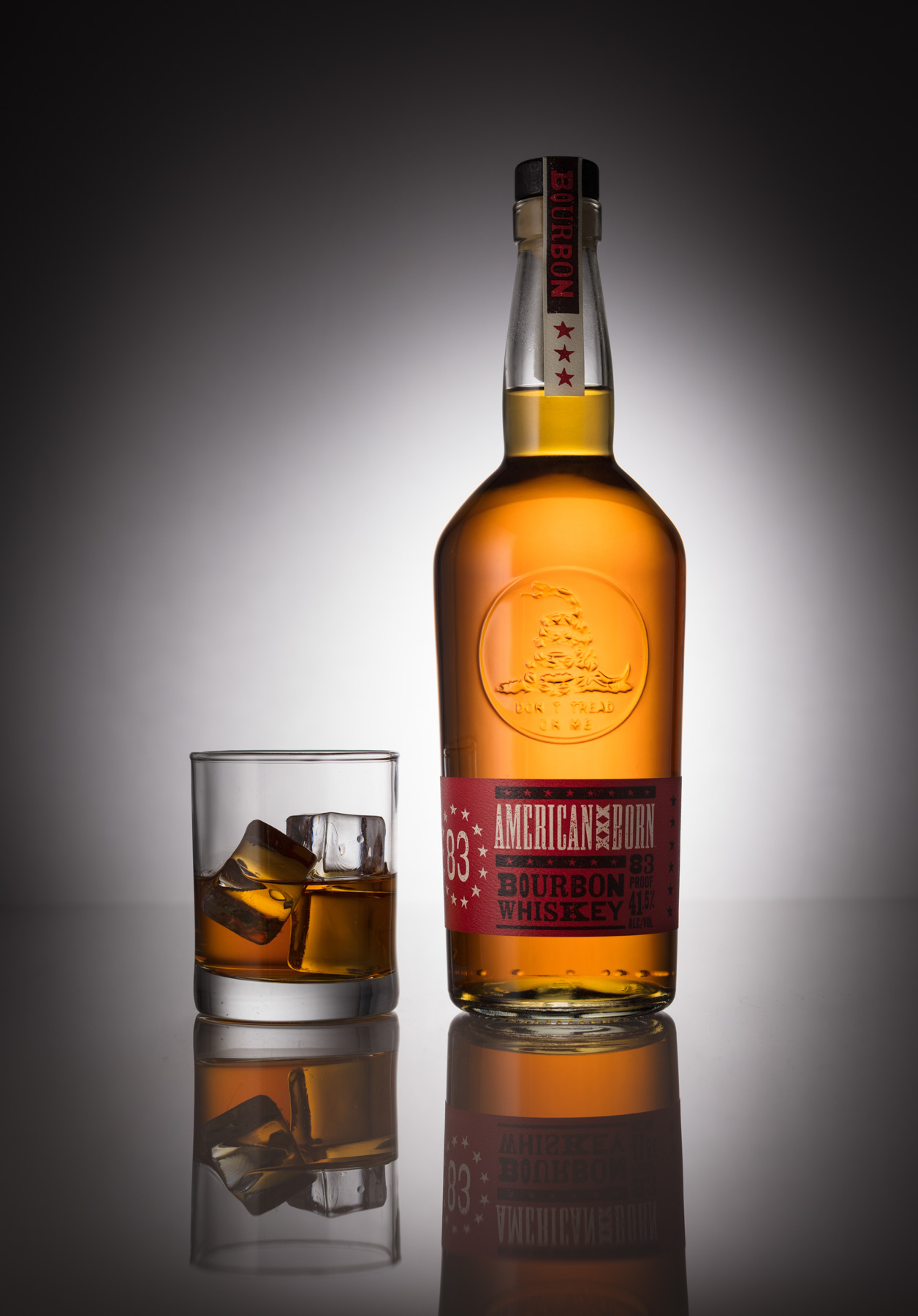 American Born Whiskey bottle beverage product photography with glass and ice on gradient background.