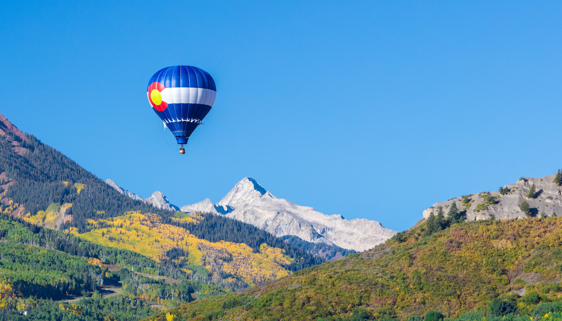 Landscape photo of hot air balloon with Colorado flag on it  above the trees during fall in Aspen, Colorado.