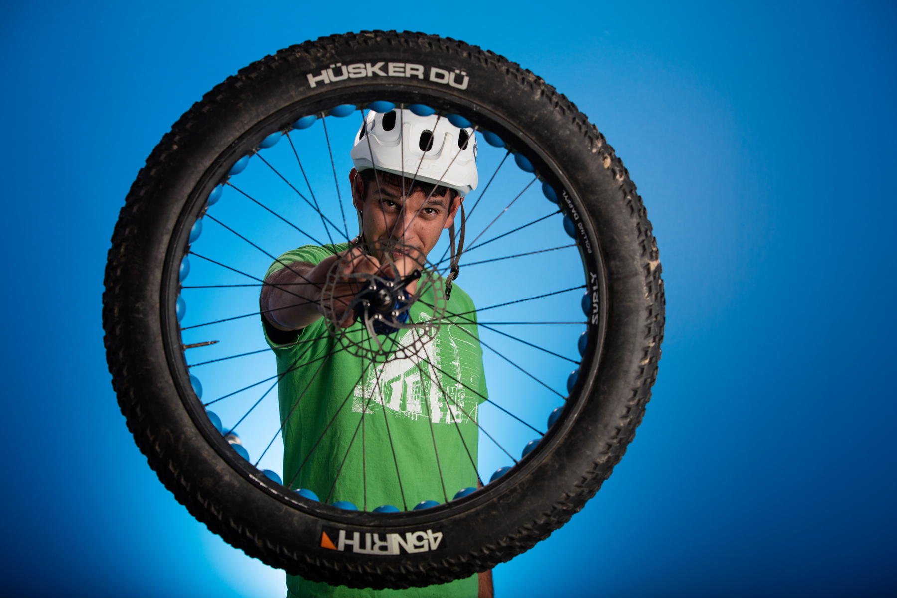 Portrait of mountain biker guy holding up wheel to the camera.
