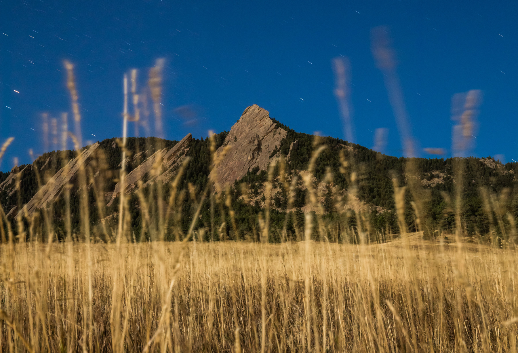 Night photo of Flatirons mountains in Boulder, Colorado at Chautauqua park with grass in foreground.