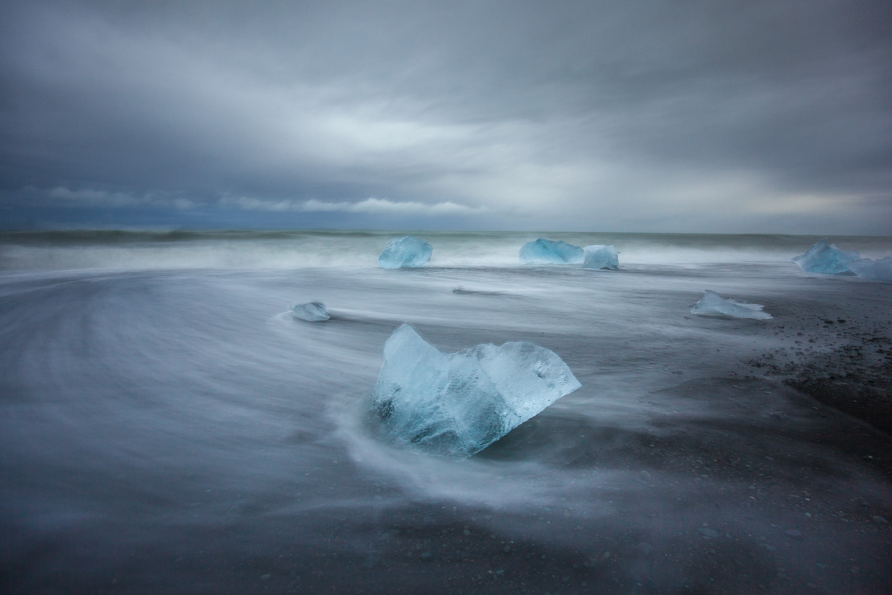 Long exposure photo of water moving passed icebergs on the beach in Jokulsarlon, Iceland.