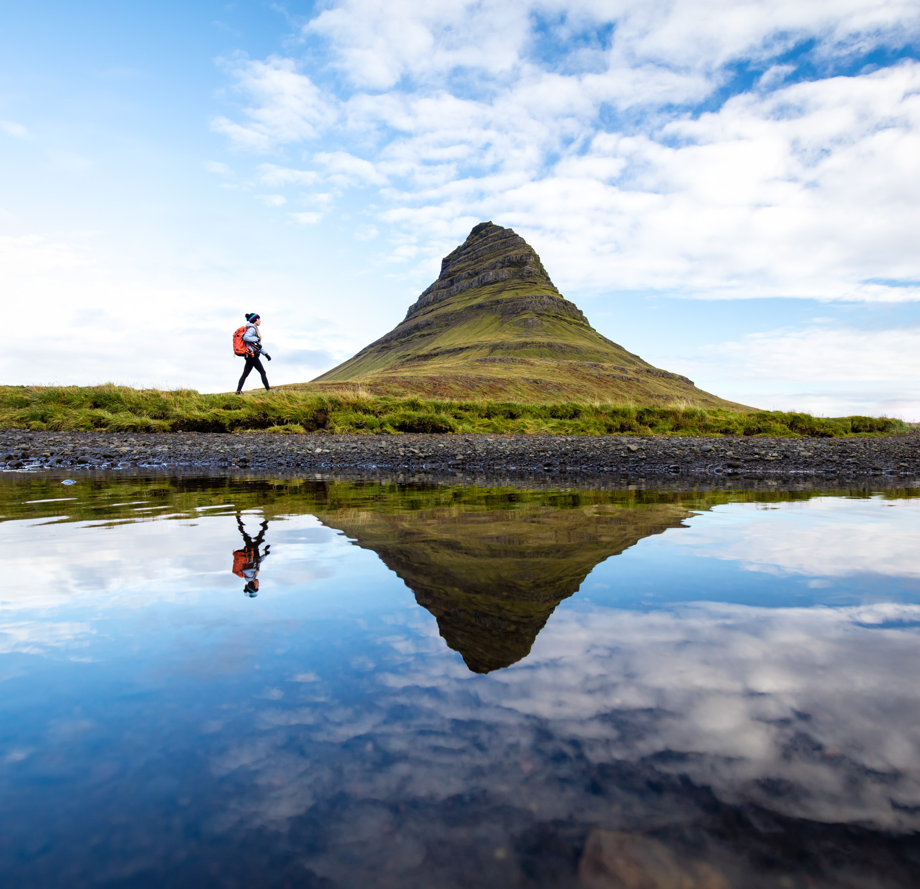 Girl walking towards Kirkjufell mountain with reflection in Iceland.