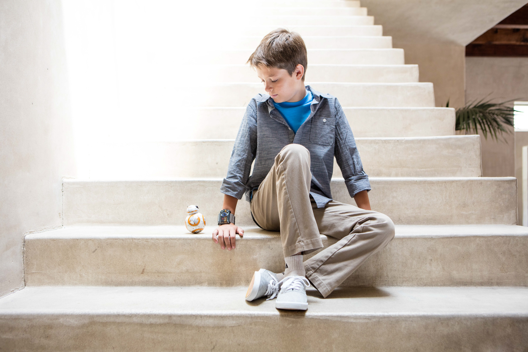 Tech lifestyle photo of boy sitting on stairs with BB-8 next to him in Venice, California.
