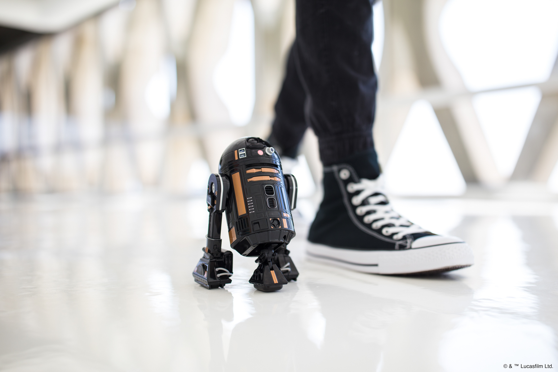 Lifestyle photo of boy walking next to Star Wars Sphero R2-Q5 in loft in Los Angeles.