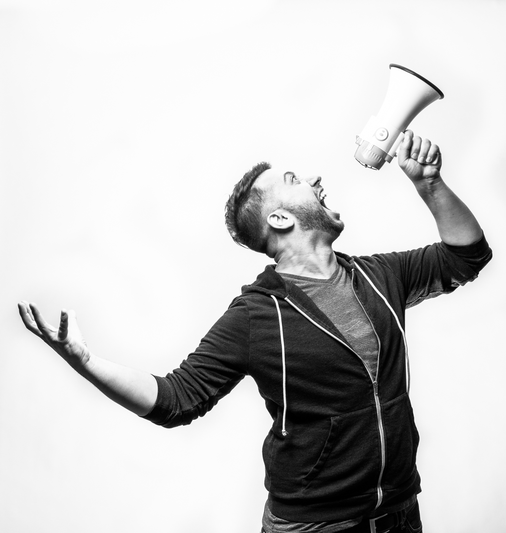 Studio portrait of man shouting into a megaphone in Boulder, Colorado.