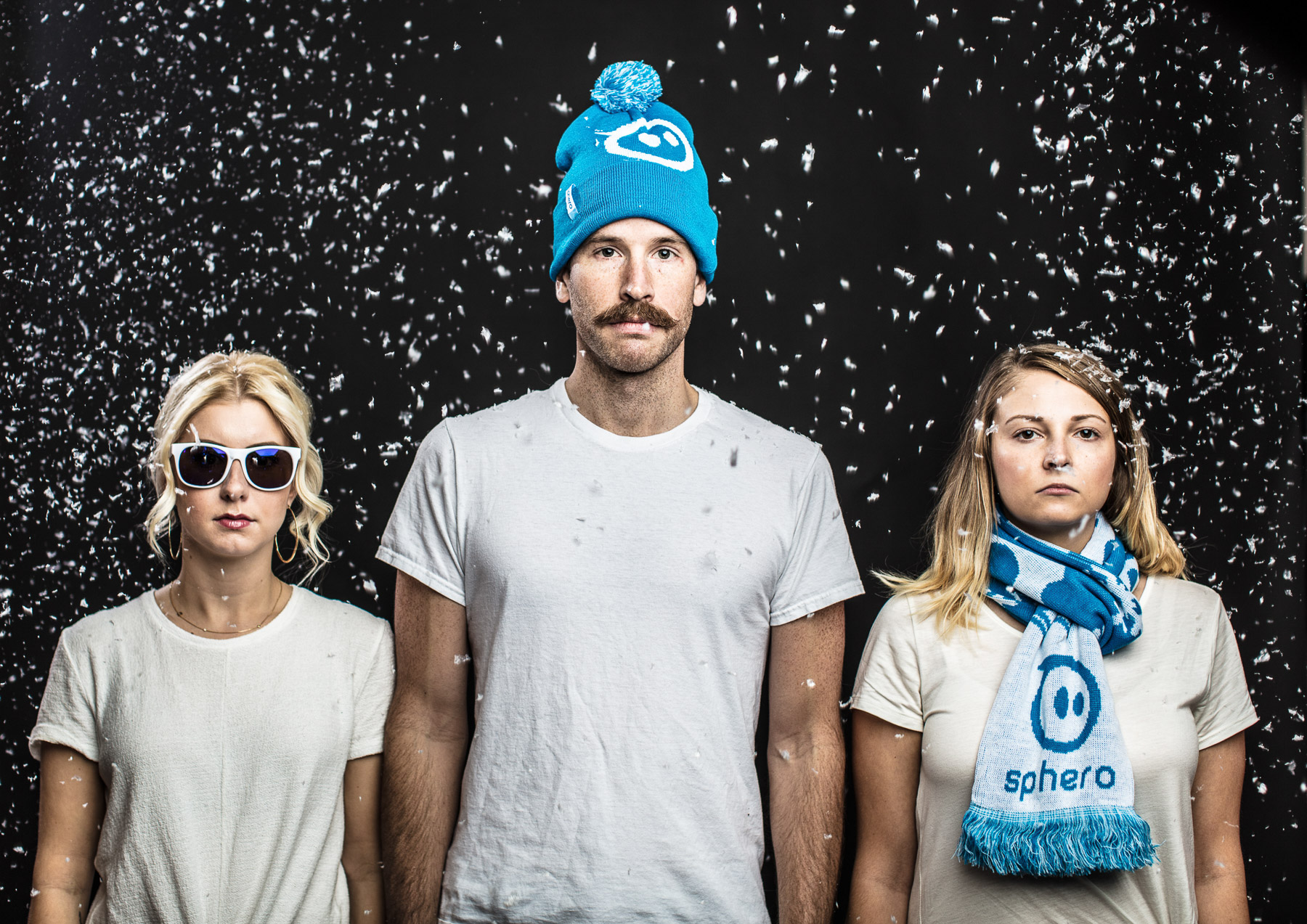 Portrait of 3 people in snowy studio scene with beanies and sunglasses on in Boulder, Colorado.