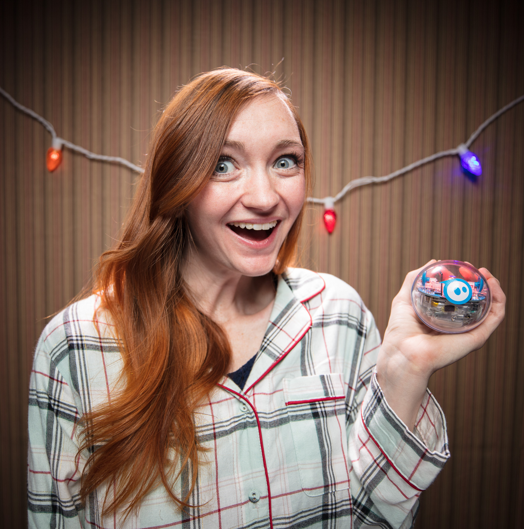 Portrait of red head girl holding Sphero SPRK+ in pajamas in Boulder, Colorado.