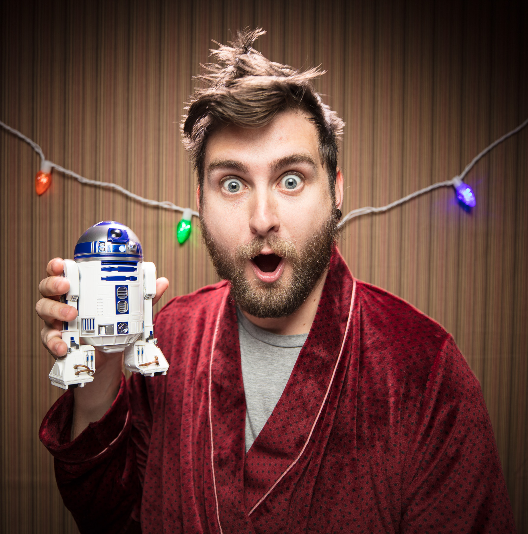 Portrait of bearded man holding Sphero R2-D2 in robe in Boulder, Colorado.